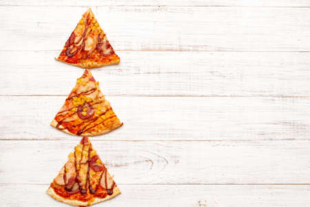 Christmas tree made of pizza on a white wooden background. Stock Photo