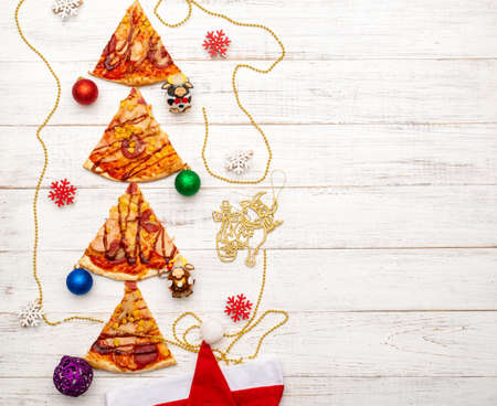 Christmas tree made of pizza on a white wooden background. 스톡 콘텐츠