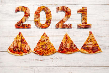 2021 and pizza. Christmas theme made from slices of pizza.