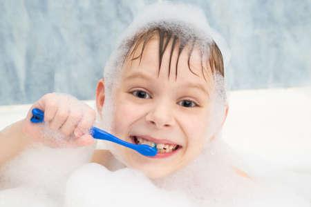 The boy in the foam is brushing his teeth in the bathroom. Dental care, hygiene.