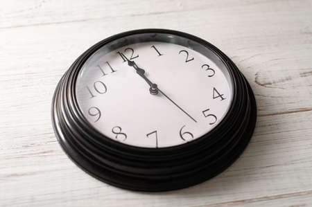 Clock on a white background. A minute to twelve.