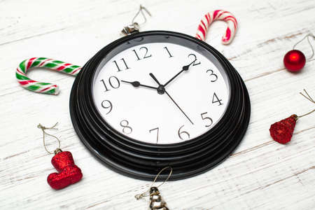 Clock on a white background and Christmas toys.