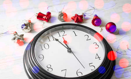 Minute twelve before the New Year. Clock on a white background and Christmas toys. Banco de Imagens