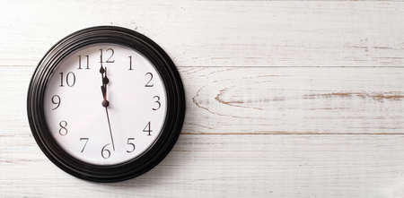 Clock on a white background. A minute to twelve. Banner. Place for your text.