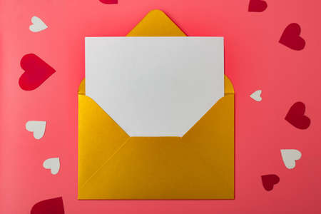 Love letter. Gold envelope on a red background with hearts. Place for your text.