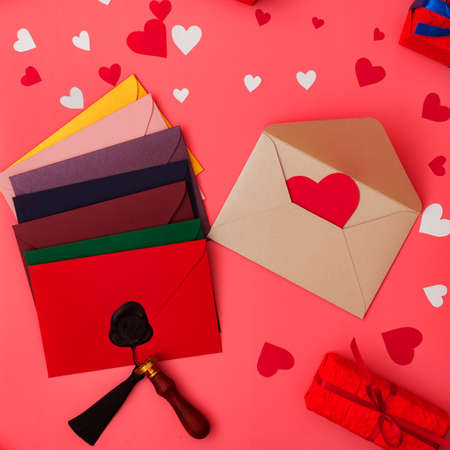 Love letters. Multicolored envelopes on a red background with hearts.