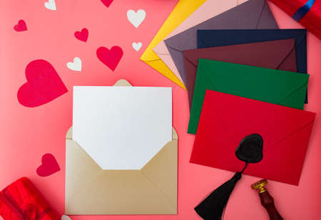 Love letter for valentine's day. Multicolored envelopes on a red background with hearts. Place for your text.