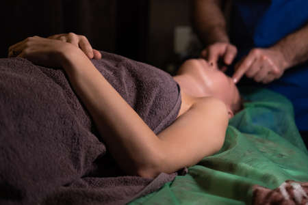 Professional facial massage. Male masseur makes procedures on a female face on a dark background