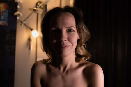 Portrait of a middle aged woman with shoulders shirtless in a dark room.