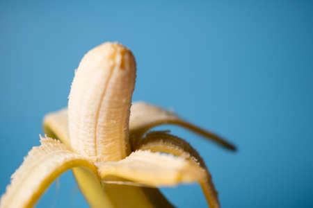 Banana, peeled in half on a blue background. Vegetarian food. Stok Fotoğraf