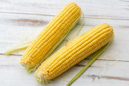 Whole corn on a white wooden background. Vegetarian food.