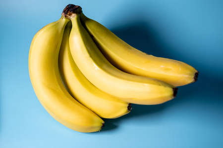A bunch of bananas on a blue background. Vegetarian food. Stok Fotoğraf