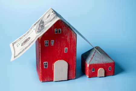 Real estate and money. A hundred dollar bill is like a roof on a toy house. Home insurance, mortgage, rental concept.