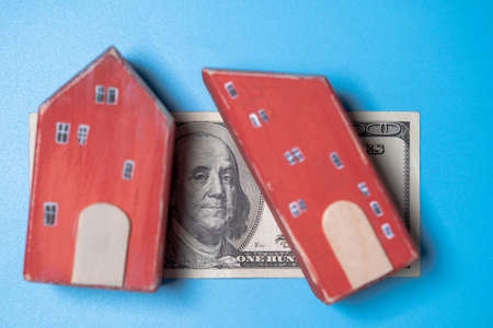 Real estate and money. Wooden toy house and one hundred dollar bill on a blue background. Savings for home construction, mortgage, rental housing concept.