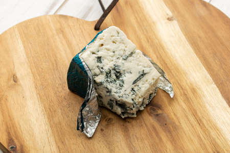 Blue cheese on a wooden background.