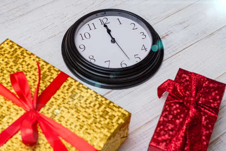 Time for gifts. Colorful gifts and a clock showing twelve.