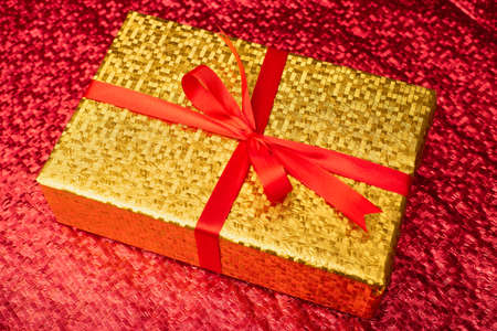 Gift in a gold package on a red background. Stok Fotoğraf