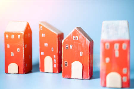 Several toy houses on a blue background. Real estate, rental, home insurance concept. Stok Fotoğraf