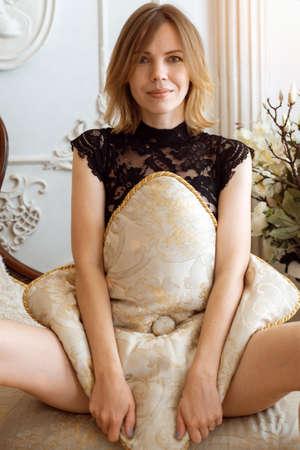 Sensual woman holding a pillow between her legs.