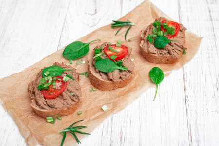 Sandwiches, canapes with chicken pate, tomatoes. On a white wooden background.