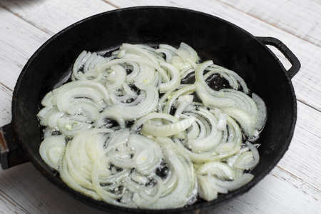 Fried onions in a pan. Cooking ingredient.