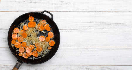 Fried onions and carrots in a pan. Roasting vegetables, preparing ingredients. Banner. Place for text.