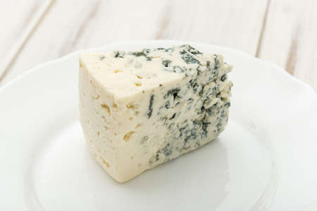 Blue cheese on a white plate on a wooden background.