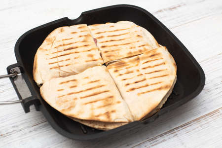 Tortilla with cheese and ham. Pita with grated cheese, ham, tomatoes on a grill pan. Stok Fotoğraf