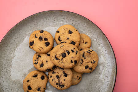 Cookies with chocolate on a plate on a pink background.