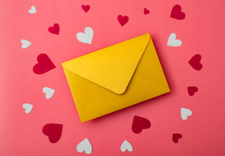 Love letter. Gold envelope on a red background with hearts. Stok Fotoğraf