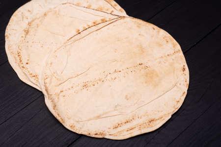 Round pita bread on a dark wooden background.