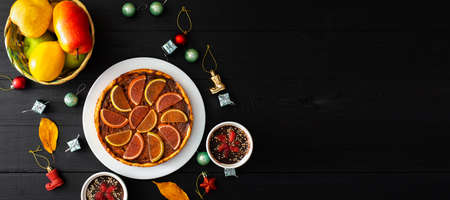 Pumpkin pie, sweet desserts and Christmas toys on a black background. Place for text.