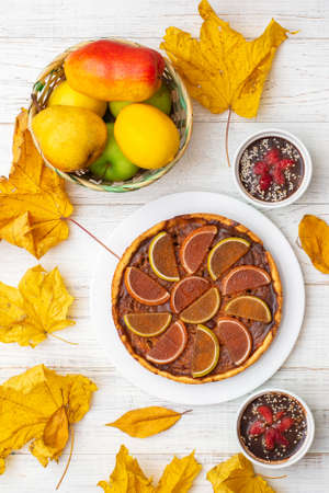 Pumpkin pie on a white wooden background. Yellow autumn leaves, apples and pears. Stok Fotoğraf