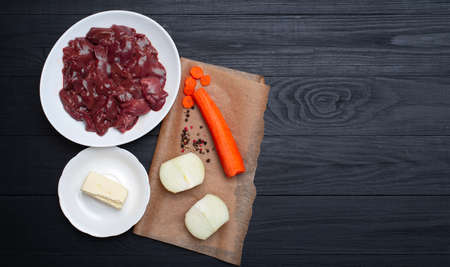 Raw chicken liver, carrots, onions, butter. Ingredients for making pate. Place for text.