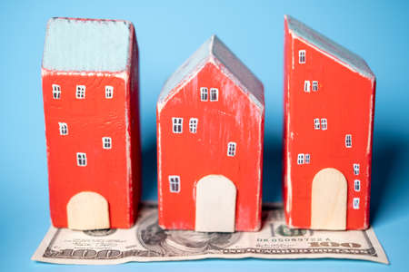 Real estate and money. Wooden toy houses and a hundred dollar bill on a blue background. Savings for home construction, mortgage, rental housing concept.