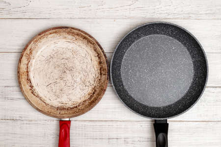 Comparison of pans. Old and new frying pan. New and old damaged non-stick coating.