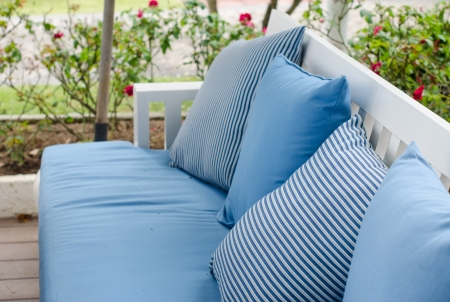 designer chair: sofa with pillows on gardenbackground