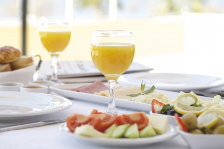 Fresh orange juice on breakfast table with tomatoes, cucumber, cheeses and olives Stock Photo