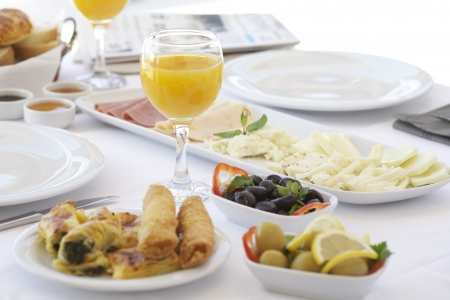 Breakfast table with cheese, tomatoes, olives, cucumber and pastries