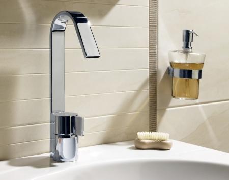 llave de agua: Grifo, jab�n l�quido y un fregadero blanco en ba�o de lujo