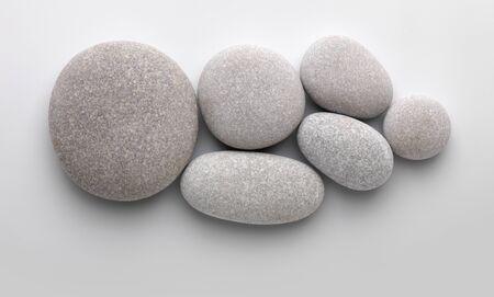 Verschillende steentjes samen op grijze achtergrond met schaduw