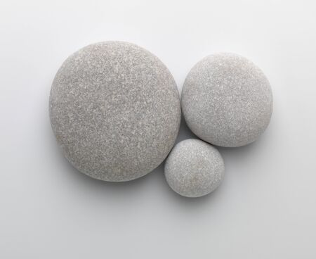 white pebble: Three pebbles together on gray background with shadow