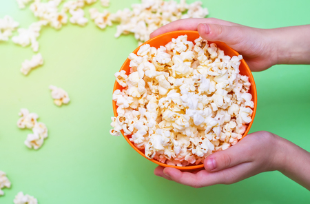 Popcorn in an orange bowl in childrens hands on a green background. Top view.