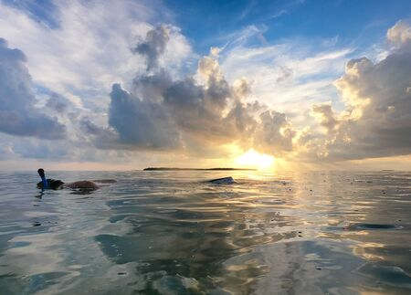 Man snorkeling in ocean with beautiful sunset in background, clouds and sun reflecting into water. Landscape with blue sky and vibrant sunset Reklamní fotografie