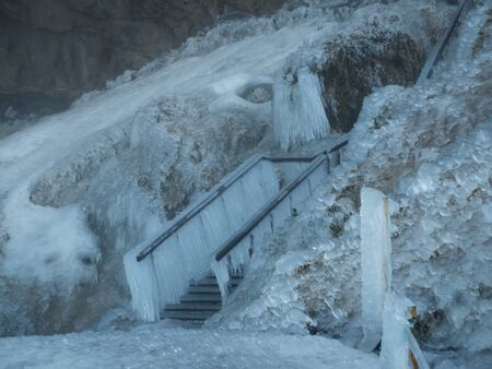 Completely frozen stairs with thick icicle near Seljalandsfoss waterfall in Iceland. Cloudy day, snow lying on ground. Copyspace, no people Stock fotó