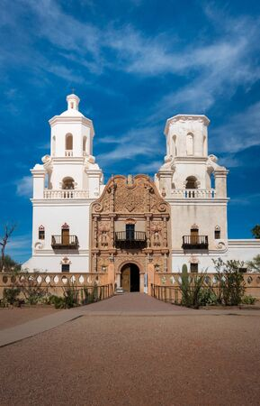 Frontal shot of Mission of San Xavier del Bac in Tucson with church tower and historic entrance. Sunny daytime shot, blue sky with few clouds. No people visible.