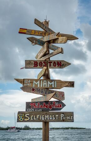Famous Key West habour sign post with distances to major american and international cities, also known as Selfiemost Point. Cloudy background with sea visible, No people.