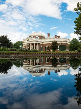 Beautiful Jefferson Monticello mansion reflecting in pool with clouds hanging above on sunny day. Reflection in calm lake mirroring landmark plantation house. No people.