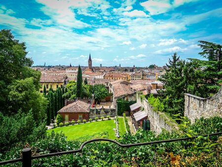 Beautiful view of Giusti gardens and lookout over italian city Verona on bright sunny day. Trees and flowers in front of Verona skyline and houses. No people.