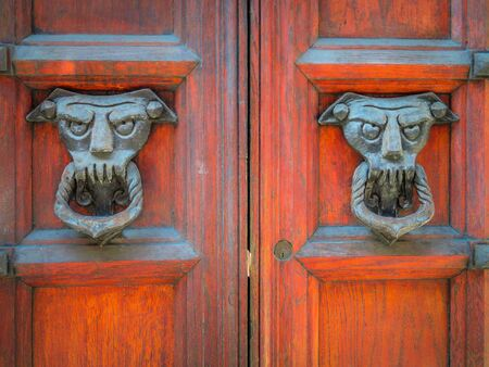 Closeup of two old and worn italian doorknockers shaped like demons or devils on red wooden door. Ferrara, Italy. Daylight shot, no people.